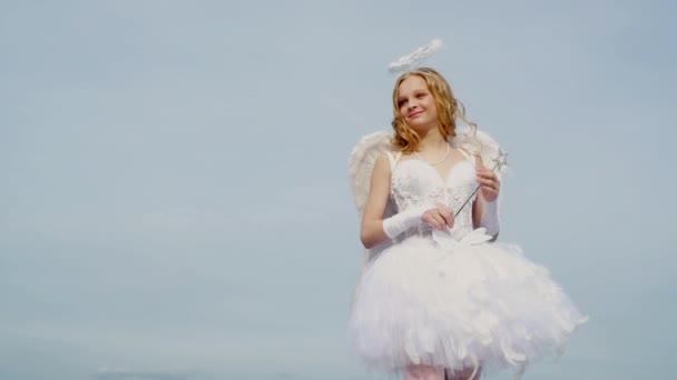 Malá Amorka míří na někoho se šípem lásky. Dítě v šatech anděla na pozadí oblohy. Bůh Lásky. Sladké andělské děvče. Milostný nápad. Nevinná dívka