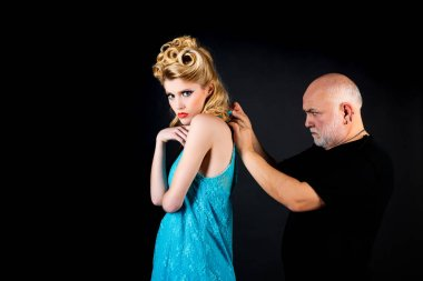 Capricious beautiful blonde woman in blue dress. Elder man with grey hair adjust necklace for his younger girlfriend. Difference of ages. Young woman with her sugar daddy concept.