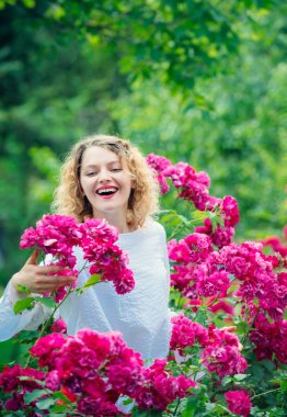 Young smiling woman surrounded rose flowers. Tender girl enjoing summer time and roseblush blossom. Rosier concept. Pink summer flowers blossom. Happy woman holding roses.
