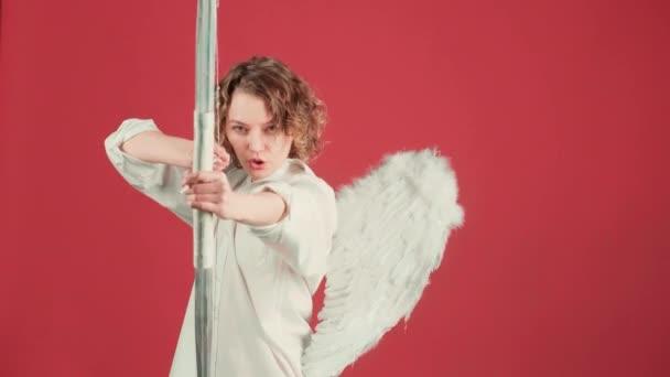 Angel dívka s lukem a šipkou přes červené pozadí. Koncept Valentines Day People. Anděl dívka s lukem a šipkou přes růžové pozadí izolované.