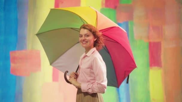 optimistische lustige Mädchen mit blinkenden Augen, während sie vor farbigem Studiohintergrund posieren. Lustige Frau mit buntem Regenschirm.