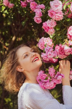 Beautiful woman holds blooming pink rosebush. Rose concept. Blossom around. Beautiful woman with pretty blooming rose flowers. Happy woman walking at rose garden.