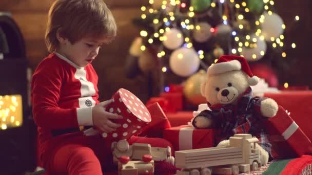 Überraschte süße Kind Mädchen öffnet ein Weihnachtsgeschenk. Weihnachtskind Eröffnungsgeschenk zu Hause. Neues Jahr für süßes Kind. Frohe Weihnachten Kind in Weihnachtsmütze mit Geschenk haben ein Weihnachten. Emotionen schenken.