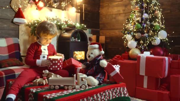 Weihnachtswunder, magische Geschenkschachtel und ein kleines Mädchen. Weihnachtskind öffnet Weihnachtsgeschenk zu Hause. Glückliches Kind mit Weihnachtsmütze und Geschenk haben Weihnachten. Emotionen schenken.