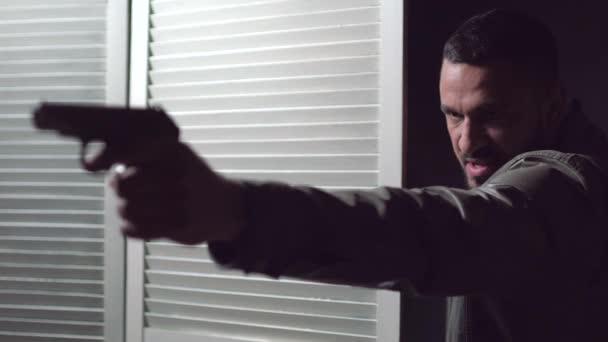 Mann schießt mit Waffe. Schwerwiegende Schießerei. Gewehr bei Fuß. Gangster mit Waffe in der Hand. Schütze.