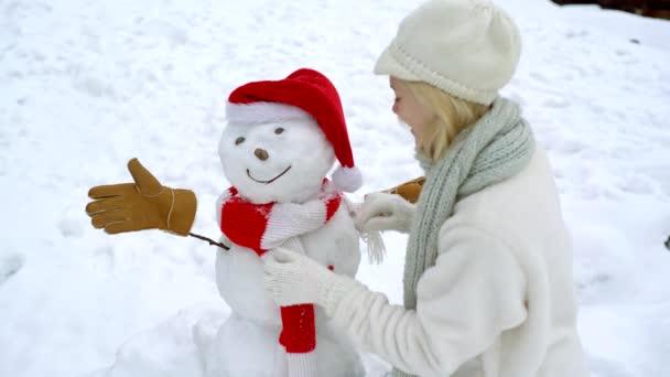 Nettes Mädchen macht Schneemann an hellen schneebedeckten Ort. Winter Outdoor-Aktivitäten Weihnachten Emotionen.