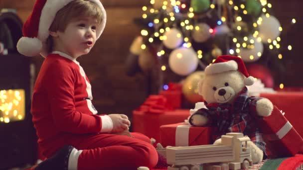 Winter Weihnachten Kinder Emotionen. Neujahrskind. Nettes Kind, das Spaß mit Weihnachtsgeschenk hat. Glückliche süße Kind in Weihnachtsmütze mit Geschenk haben ein Weihnachten. Innenraum.