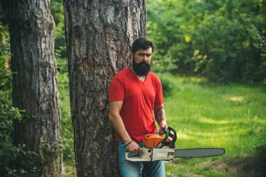 Lumberjack worker with chainsaw in the forest. Handsome young man with axe near forest. Stylish young man posing like lumberjack. A handsome young man with a beard carries a tree.