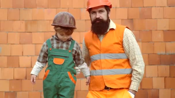 Malý kluk a jeho otec stavěli dům společně. Chlapec a otec si doma hrají na stavitele. Budova otce a syna. Dítě s rodiči v Hard Hat hrát stavební bloky.