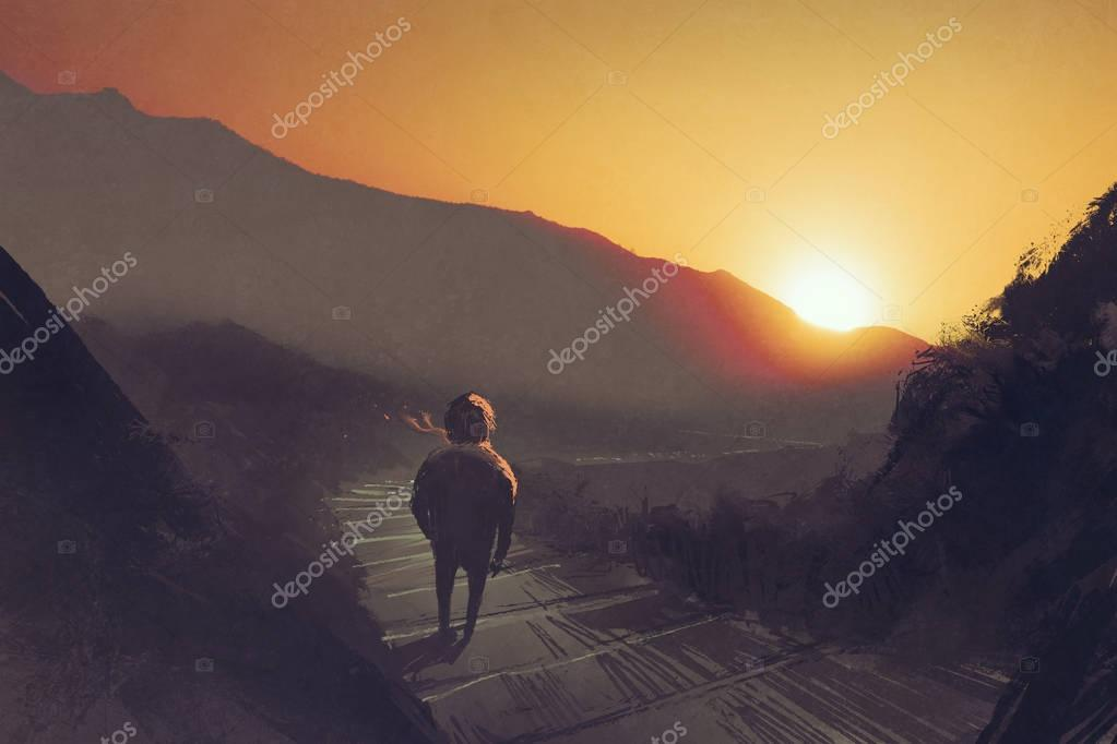 man standing on mountain pathway stairs looking at the sunset