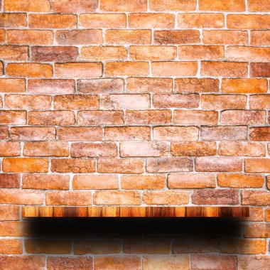 Empty top of wooden shelf with red brick wall.