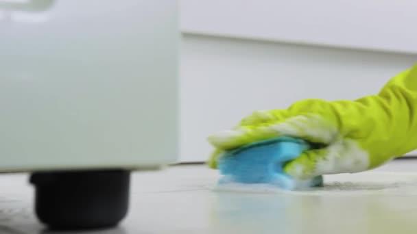 Žena ve žlutých gumových rukavicích čistící podlahy s houbou s čisticím prostředkem