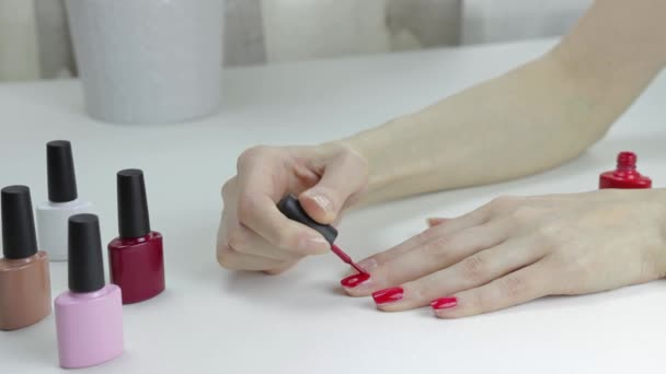 Mladá žena si lakuje nehty červeným lakem na nehty. Kosmetický zákrok