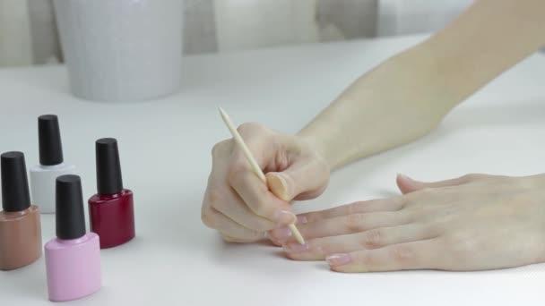 Mladá žena odstraňuje kůžičky holí na manikúru. Kosmetický zákrok