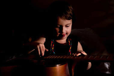 A little pretty girl enjoys playing guitar. Light and shadow concepts.