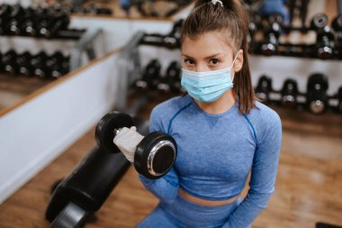 Young beautiful caucasian woman in protective masks  in the gym with weights stock vector