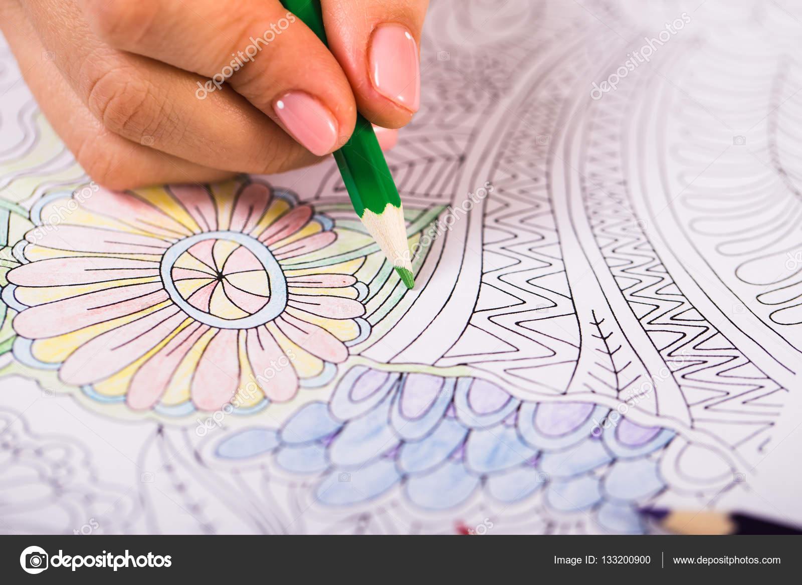 Niña pinta un libro para colorear para adultos con lápices de ...