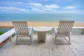 Sedia di spiaggia di legno bianca vicino mare in estate