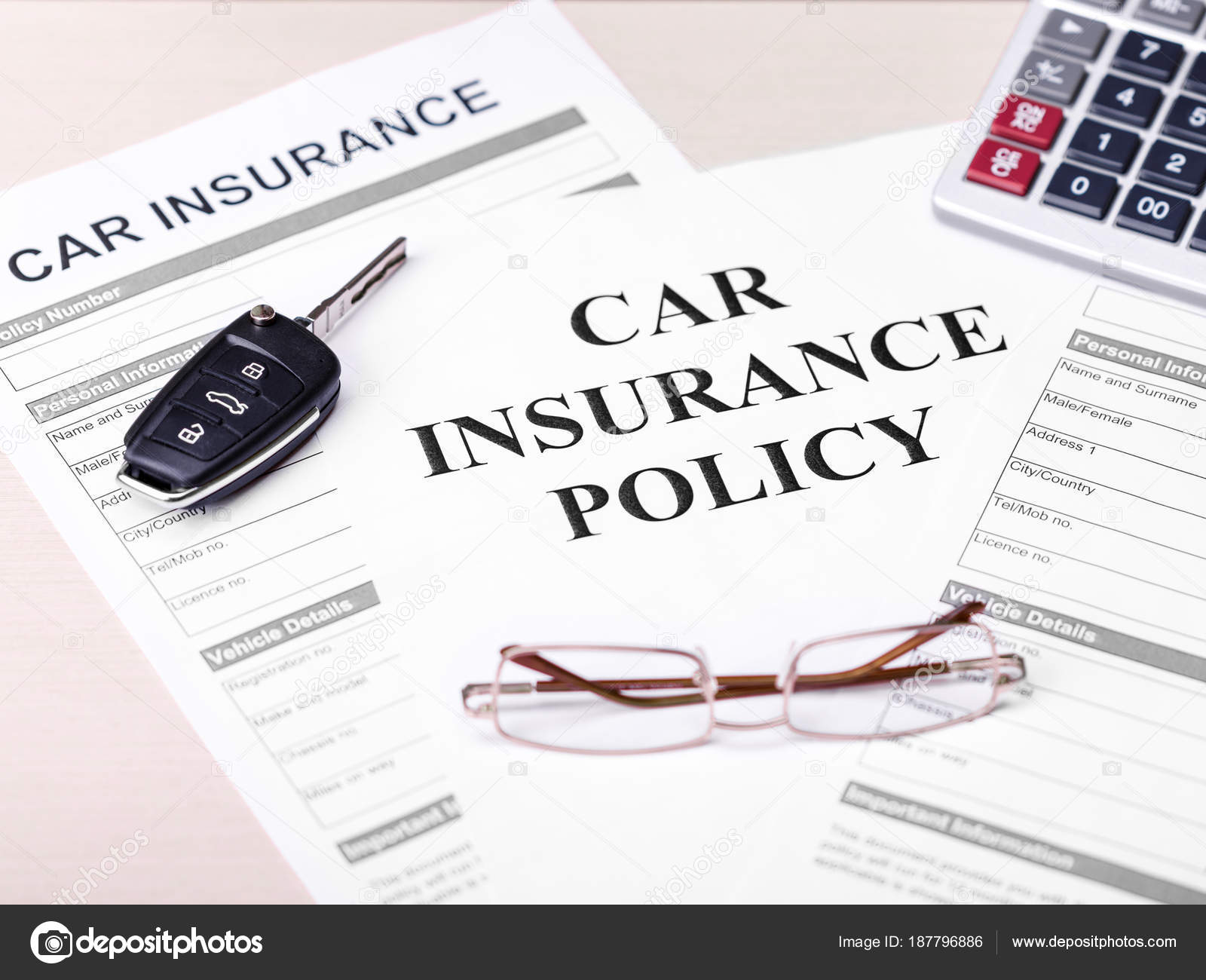 Car Insurance Policy Document Key Glasses And Calculator On Table