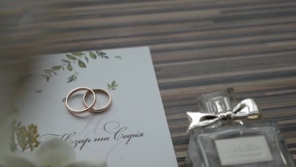 wedding arrangement of flowers, invitations cards, wedding rings and perfumes
