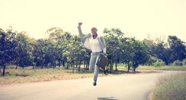 Businessman at outdoors jumping with case