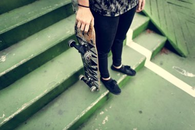 Woman standing with skateboard
