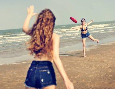Girls playing frisbee on beach