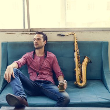 Musician sitting on sofa with Saxophone