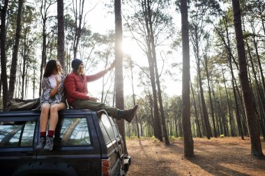 Couple Sitting on Car in Forest