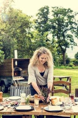 Woman Preparing Table For Dinner