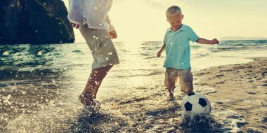 Father and son playing football on beach