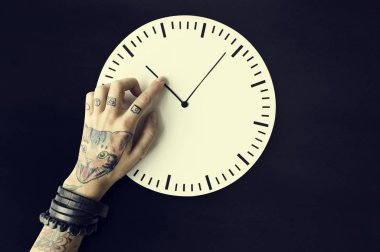 hand in tattoos with clock