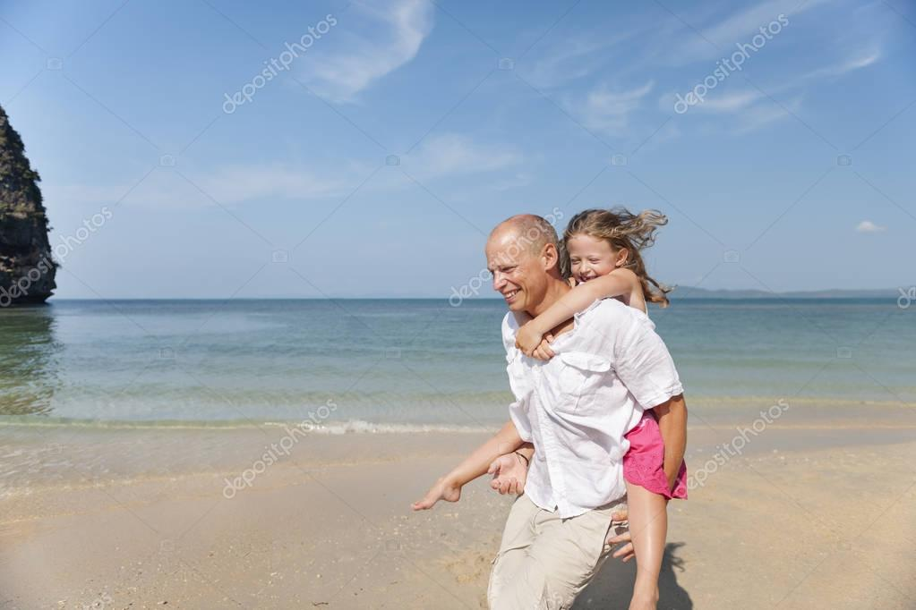 Father and daughter having fun on beach