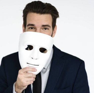 Young man holding mask