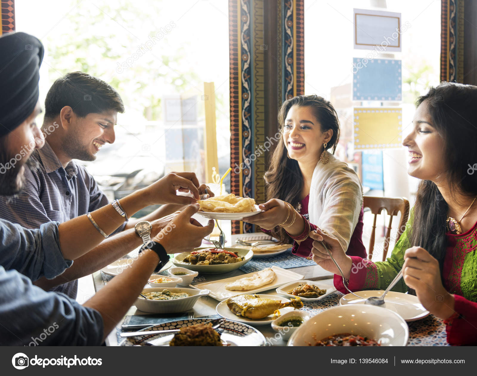people eating indian food in restaurant � stock photo