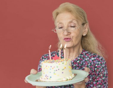 Senior Woman blowing candles