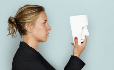 Businesswoman holding mask