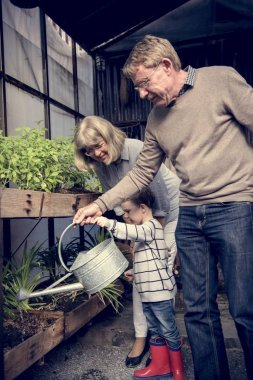 Grandparents with grandson Watering Plant