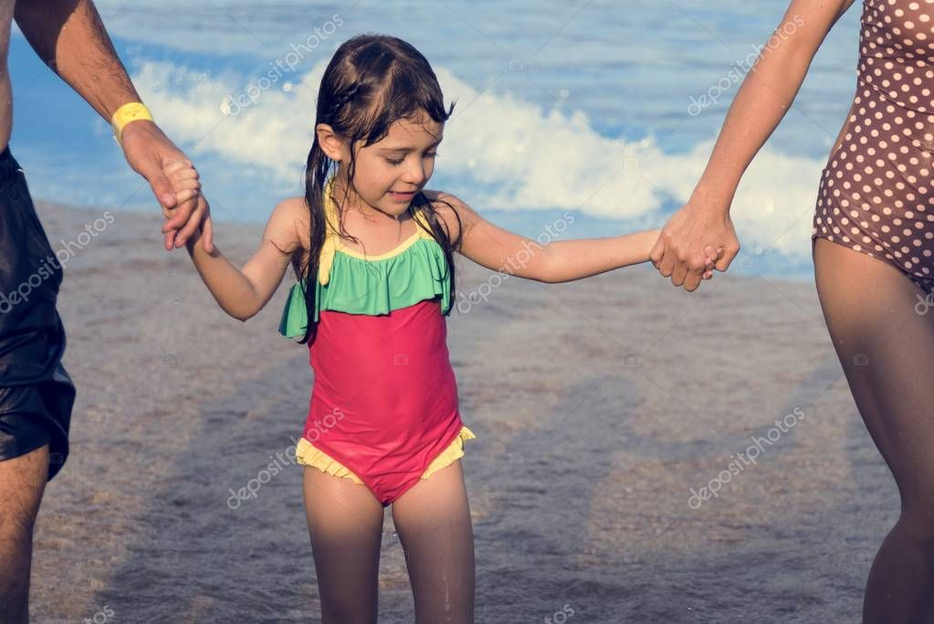little girl walking with parents on beach
