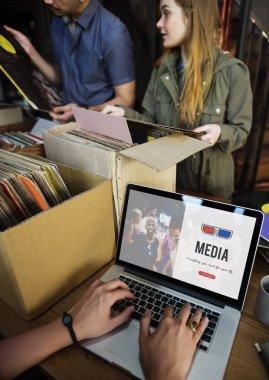Man at vinyl shop using laptop