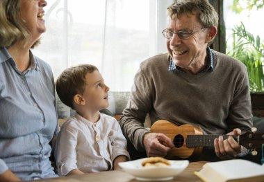 Grandparents and grandson playing ukulele