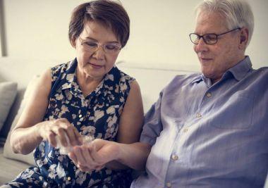 Sick Senior couple holding pills