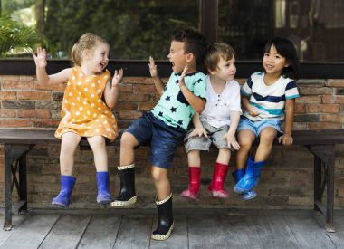 Group of kindergarten kids siting outdoors