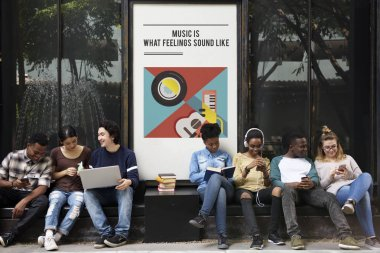 Young students siting near placard