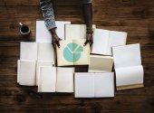 Hände am Tisch mit vielen Büchern