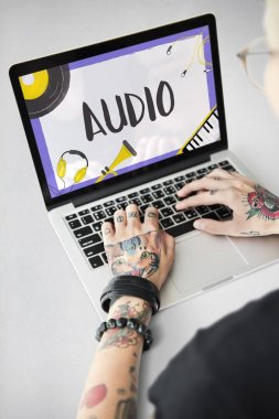 Tattooed woman hands typing on laptop
