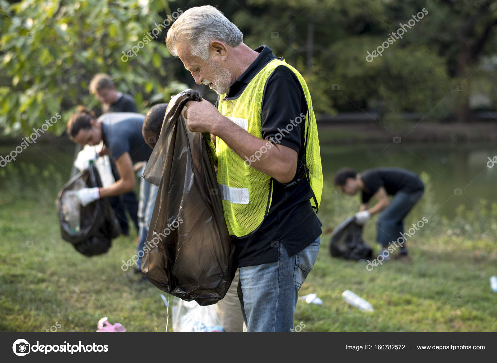 Friendly Diverse Volunteers Pick Up Trash In Local Park Stock Photo