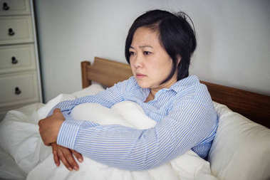 Asian upset woman pondering in bed