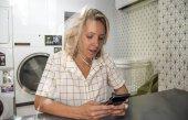 Fotografia Donna caucasica utilizzando il telefono cellulare presso una lavanderia self-service