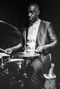 african drummer performing on stage, black and white